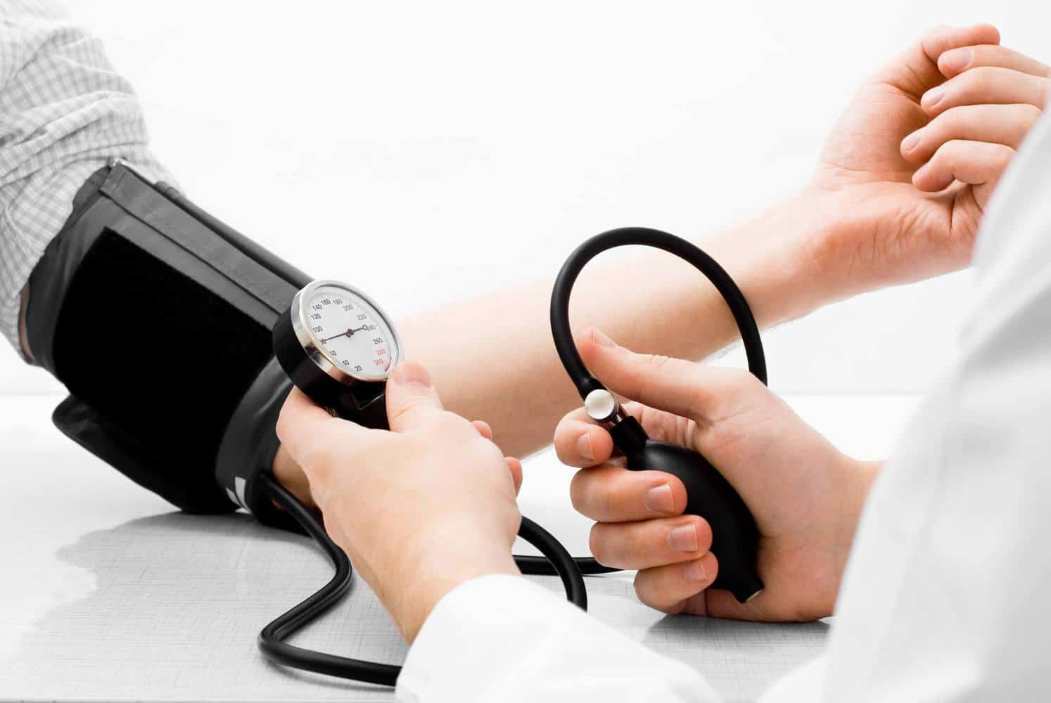 A doctor measuring blood pressure with a device.
