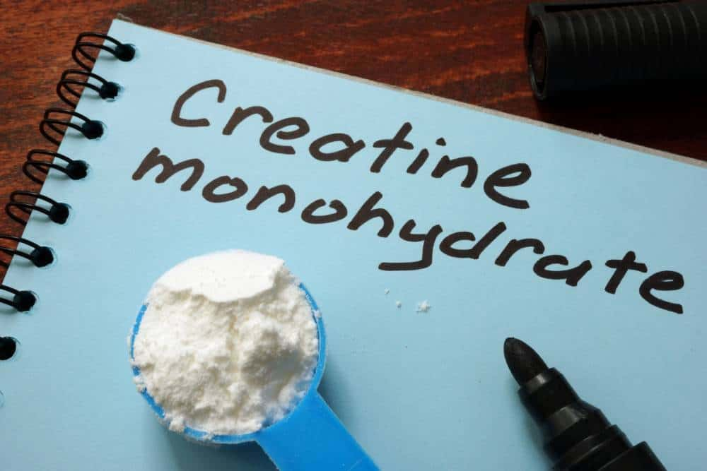 Creatine Monohydrate written on a paper next to a spoon of powder.