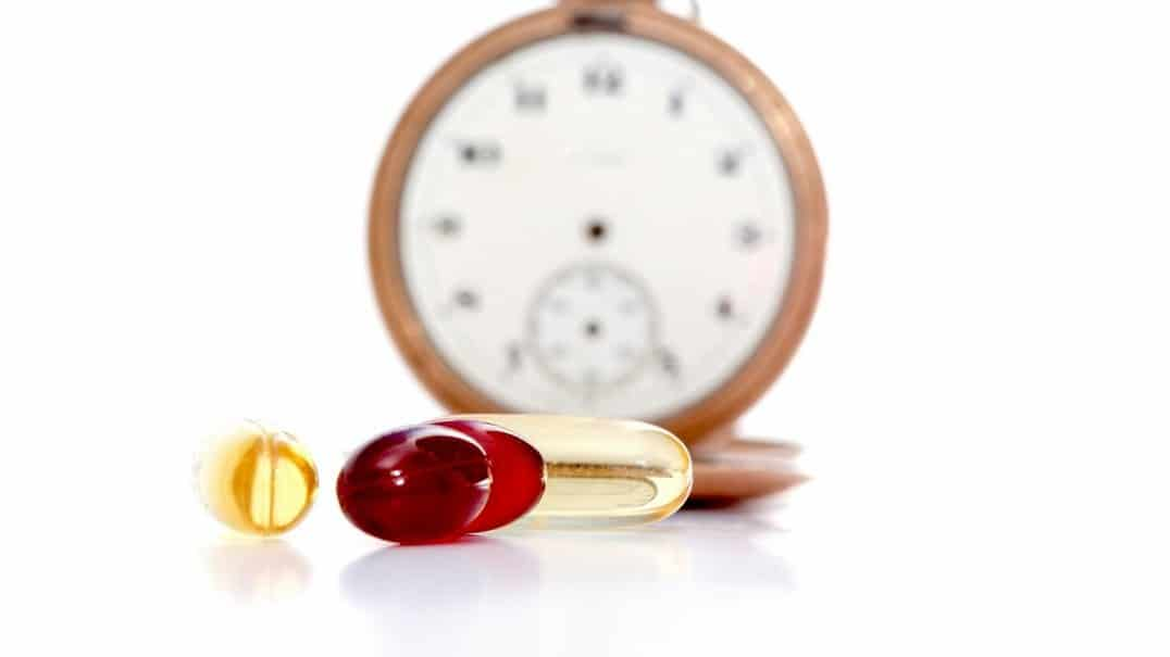 Capsules with a clock in the background.