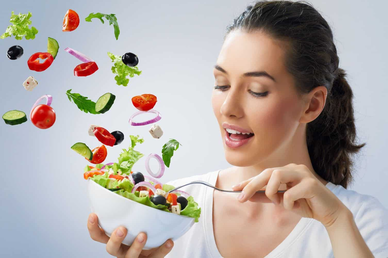 A woman getting a bowl of vegetables