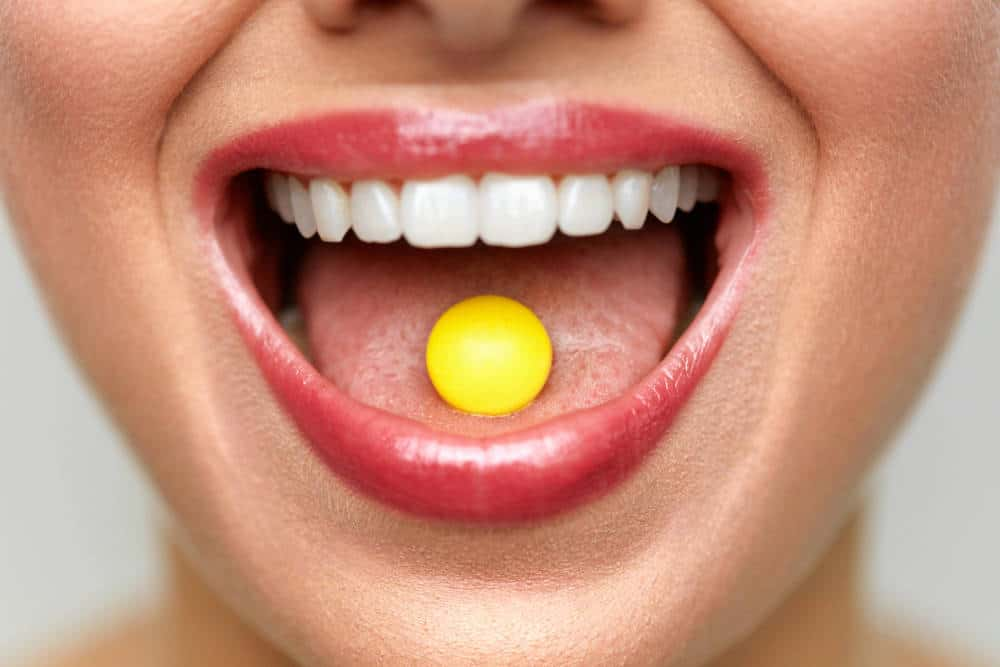 A gummy tablet vitamin on a woman's tongue.