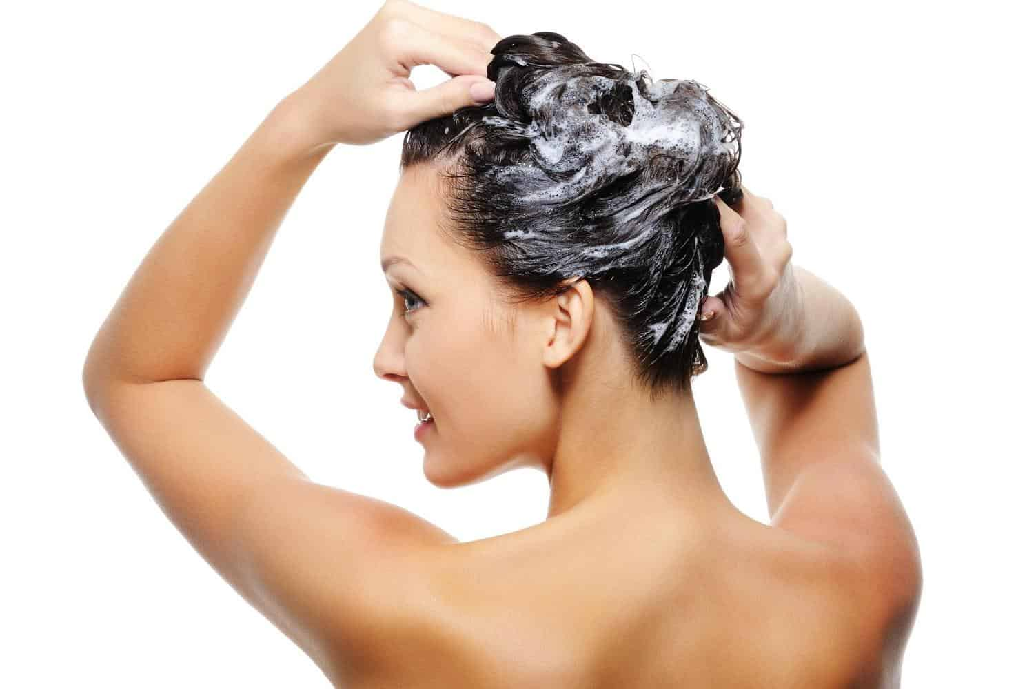 A woman applying shampoo to her hair.