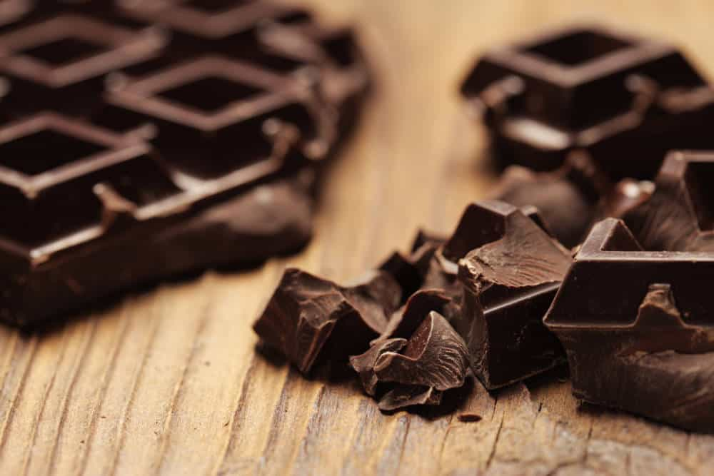 Pieces of dark chocolate on a wooden background