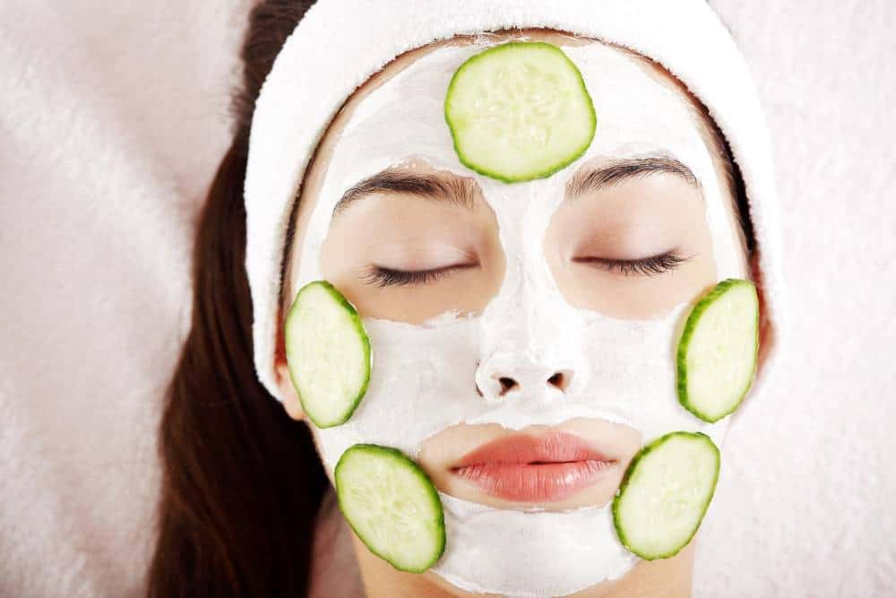 A woman with a cucumber and cream facemask.