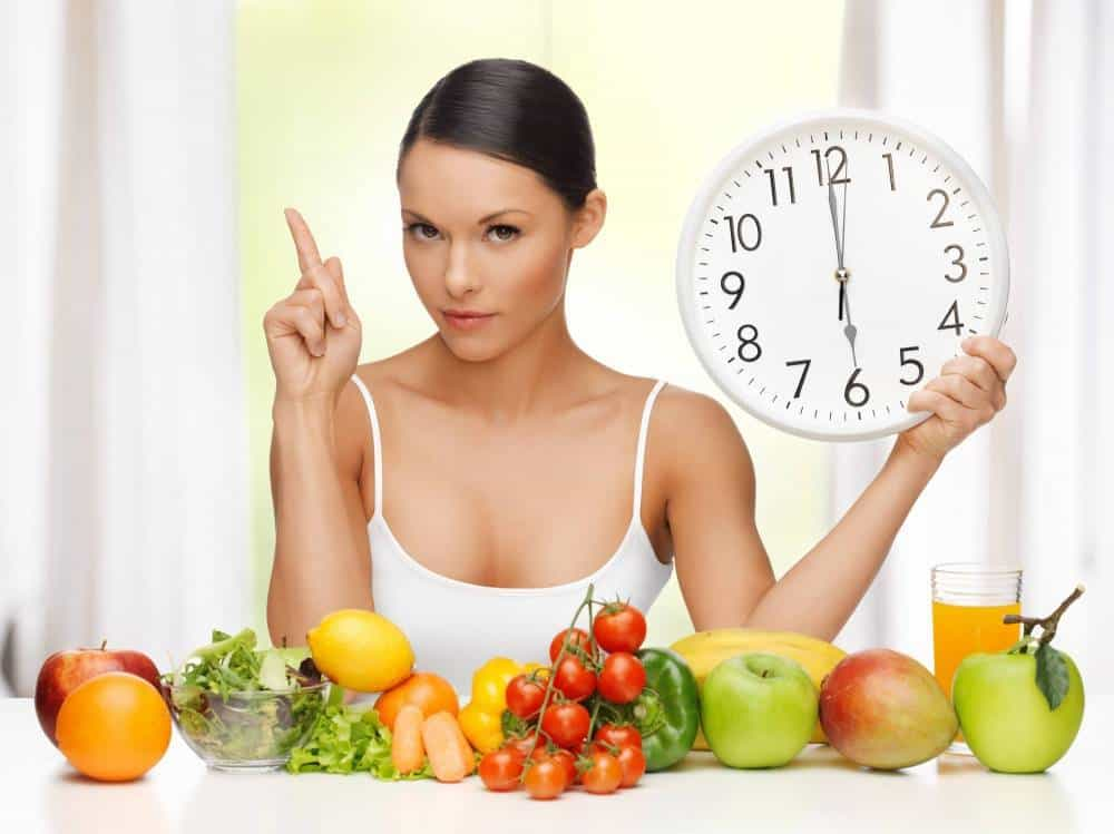 A woman looknig into the camera while holding a clock, surroudned by fresh fruit and vegetables.