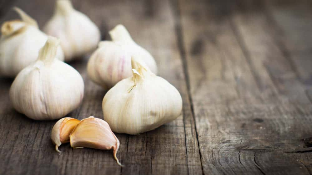 Several fresh garlic cloves on wood background.
