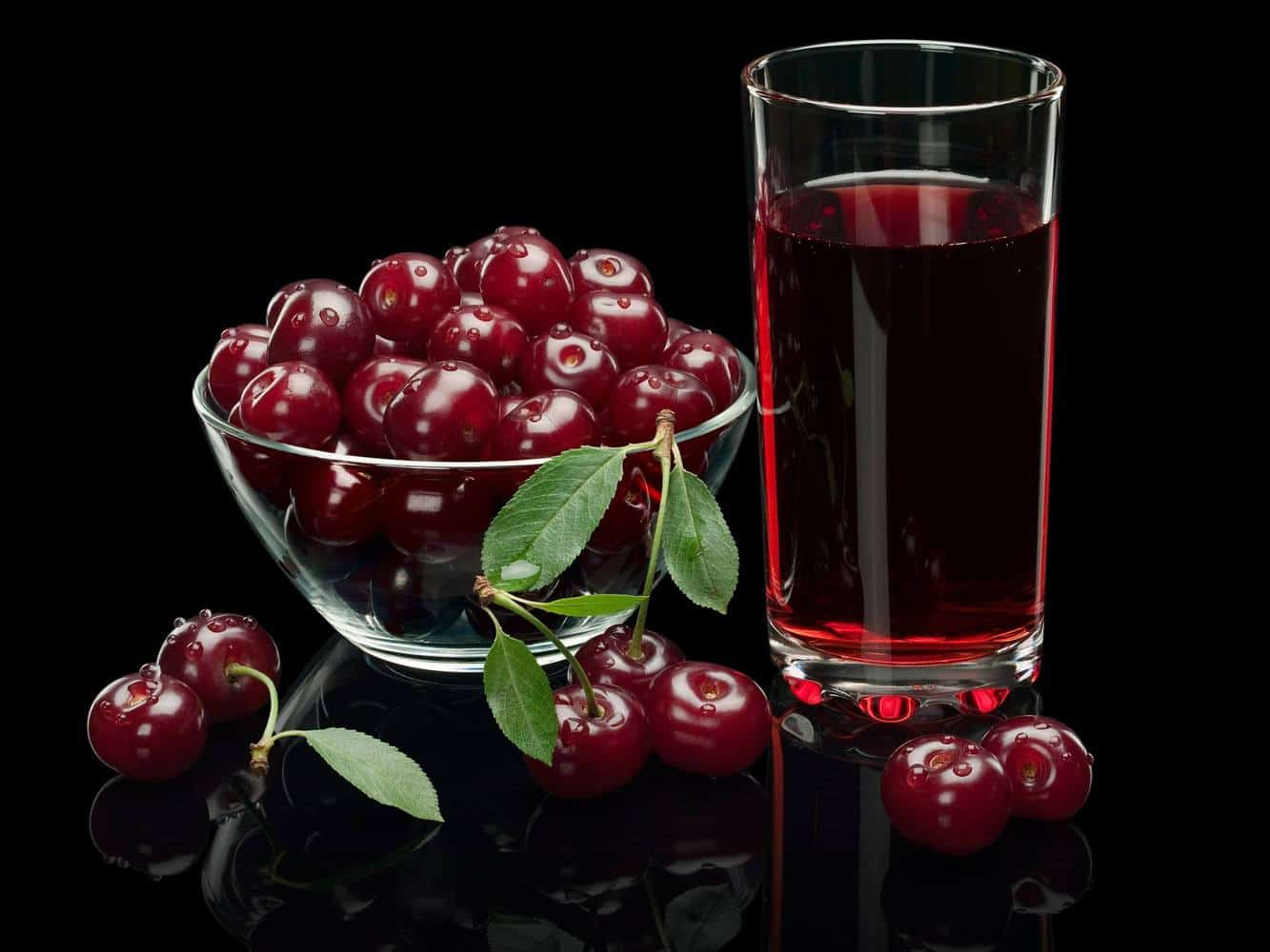 A glass of black cherry juice next to a bowl of black cherries.