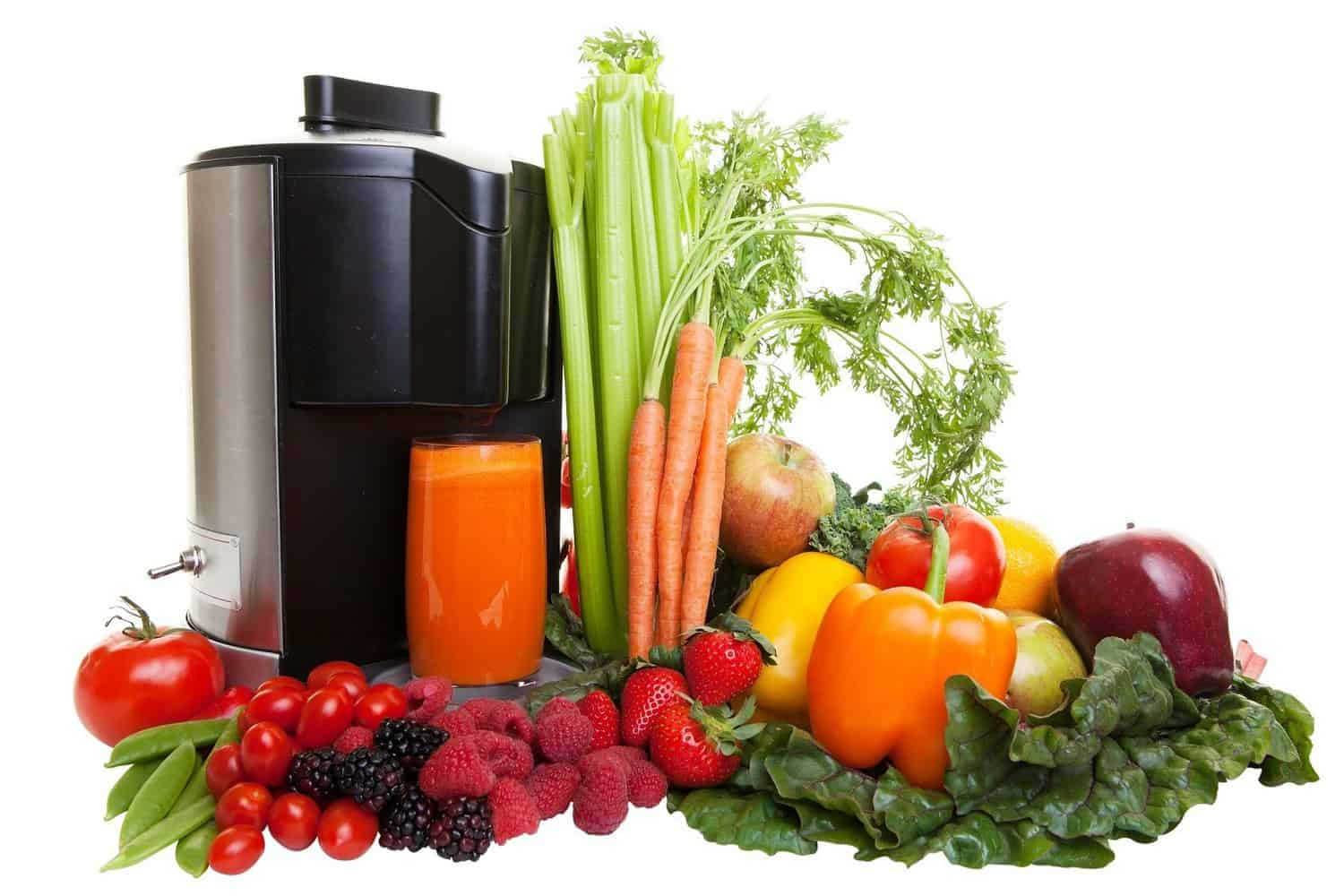A juicer surrounded by fruit and vegetables.