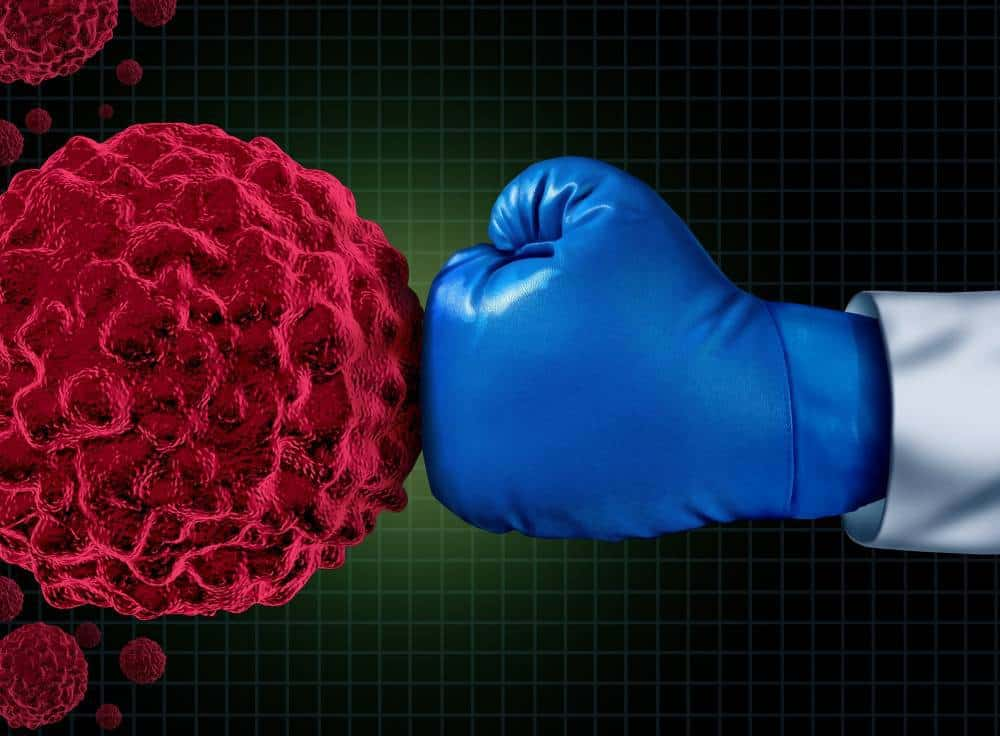 A boxing glove hitting cancer cells.