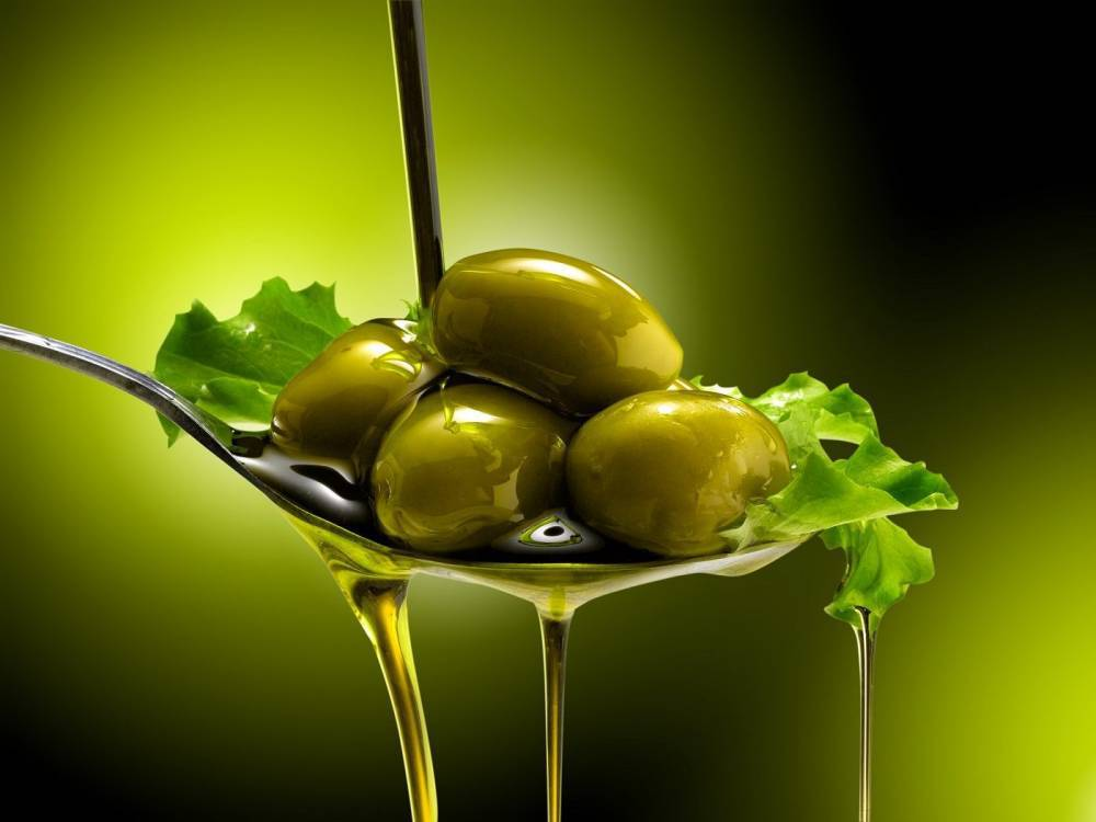 Olives in a spoon covered by oil.