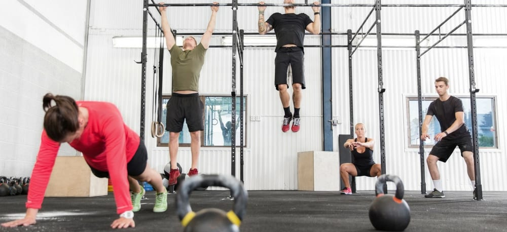 People doing cross fit exercises in a gym.