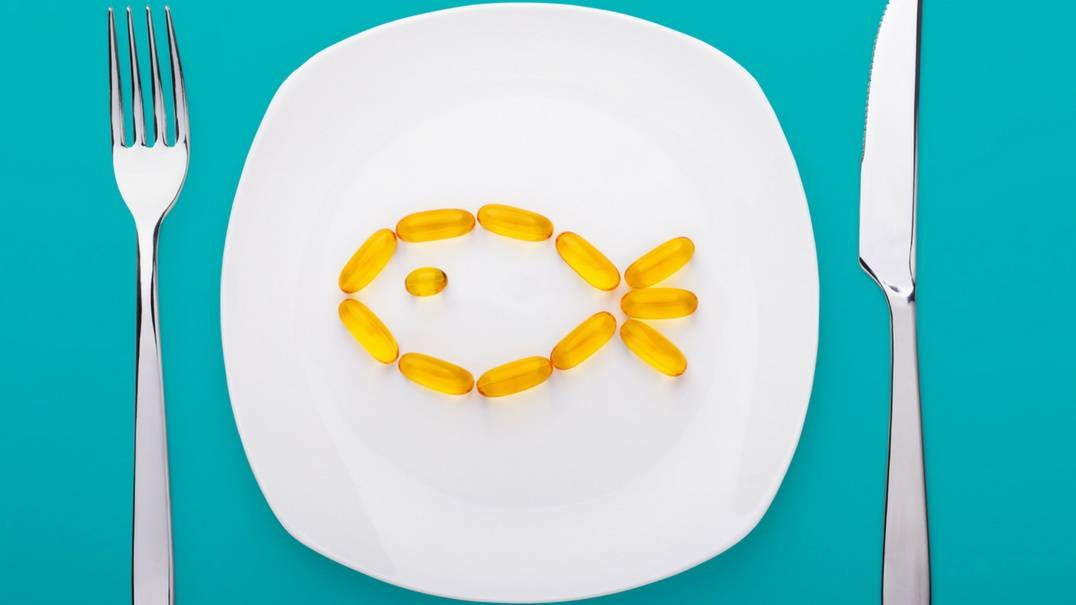 A plate with fish oil capsules shaped like a fish.