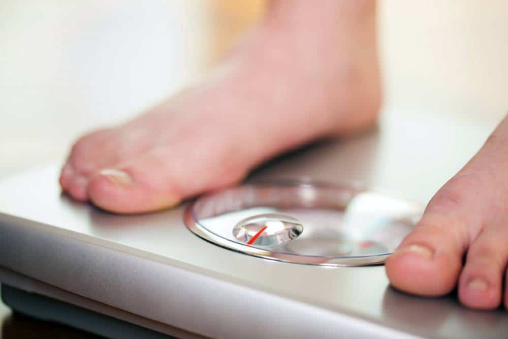 A person checking their weight using a bathroom scale.