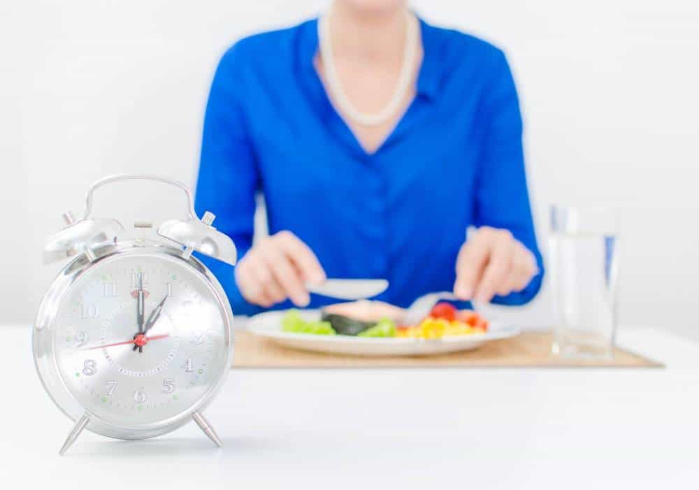 An alarm clock with a woman eating in the background.