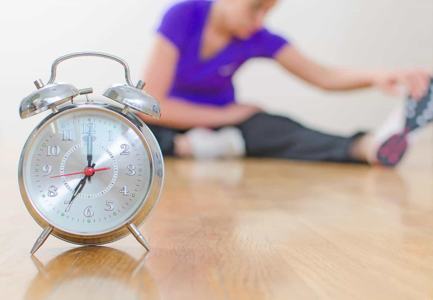 An alarm clock with a woman stretching in the background.