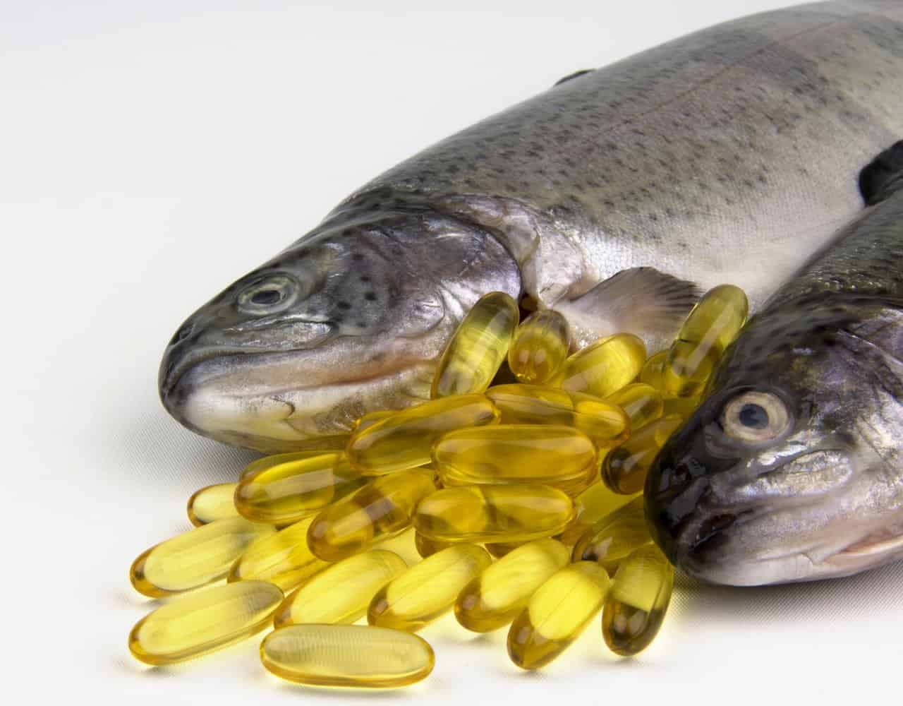 Fish oil capsules next to raw fish.