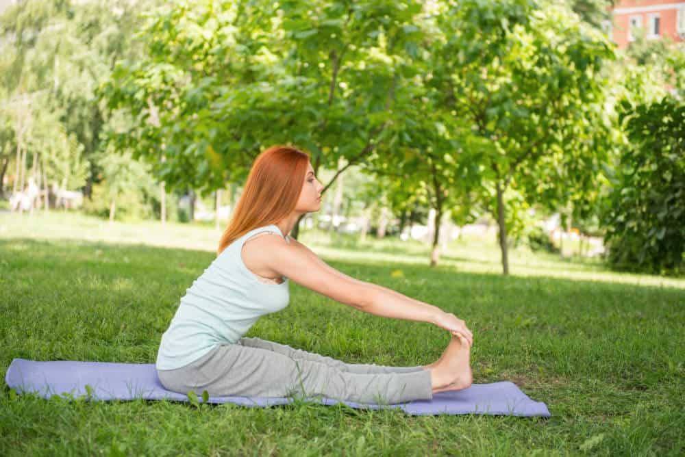 A woman stretching in a park.