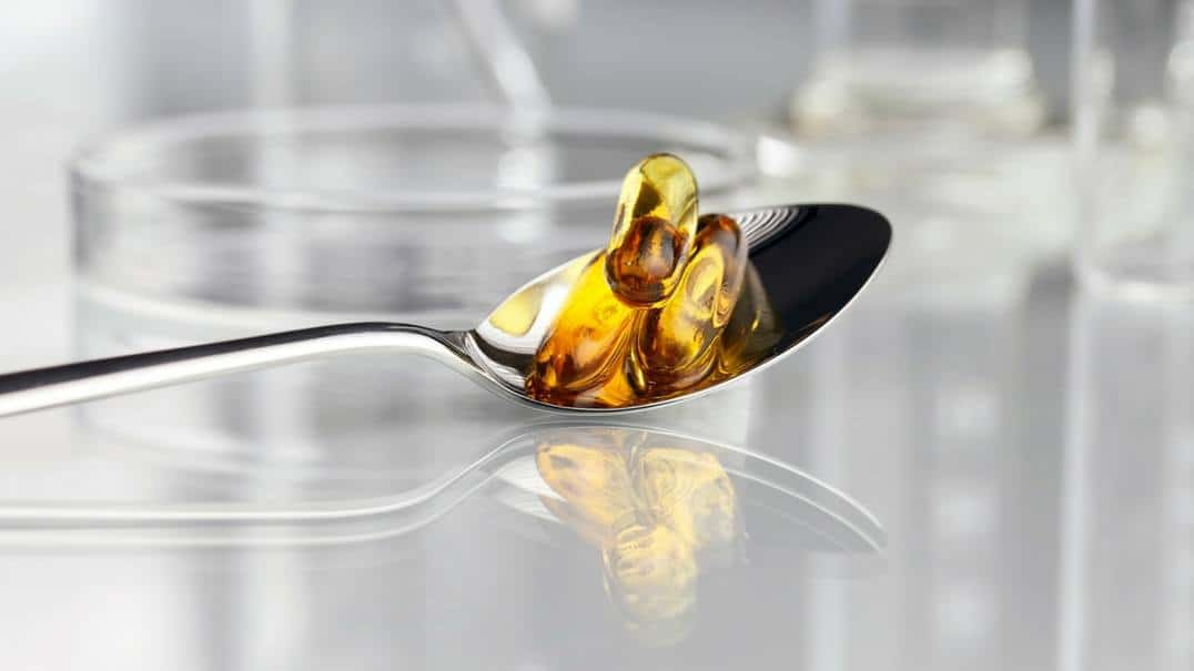 Fish oil capsules in a spoon.