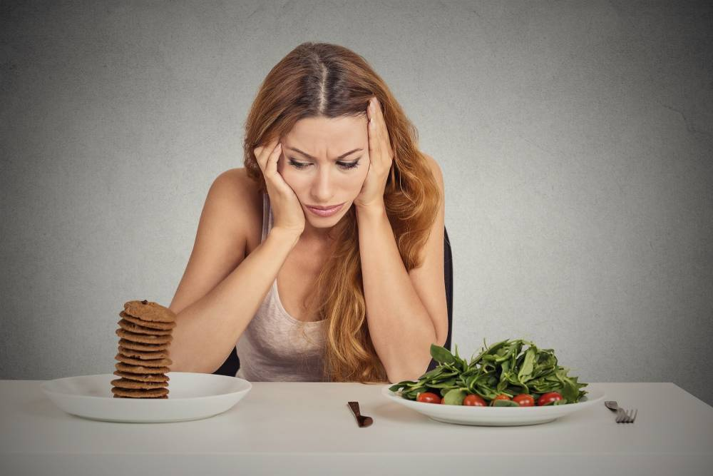 A woman struggling to decide between a plate of carbs and a plate of salad.