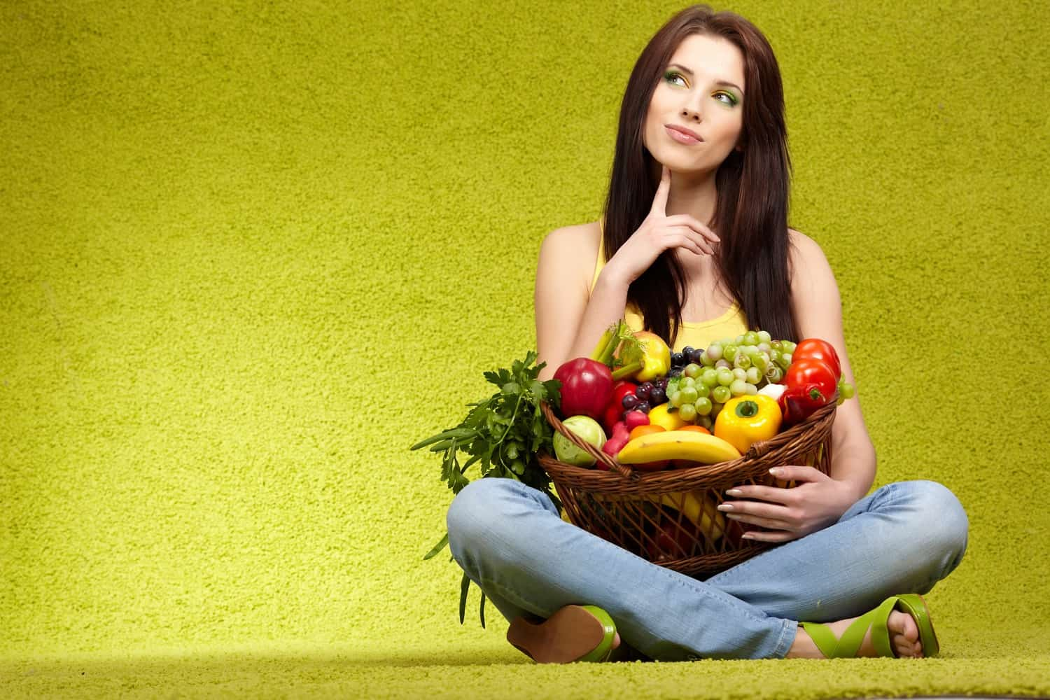 A woman with a basket of fruit and vegetables.