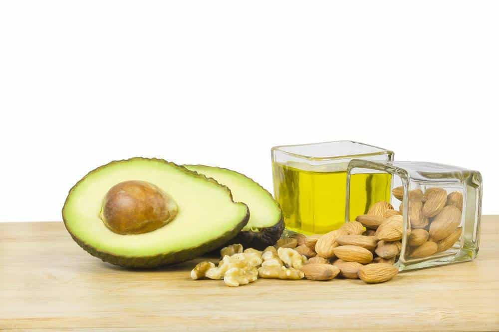 Avocado next to some nuts and avocado oil.