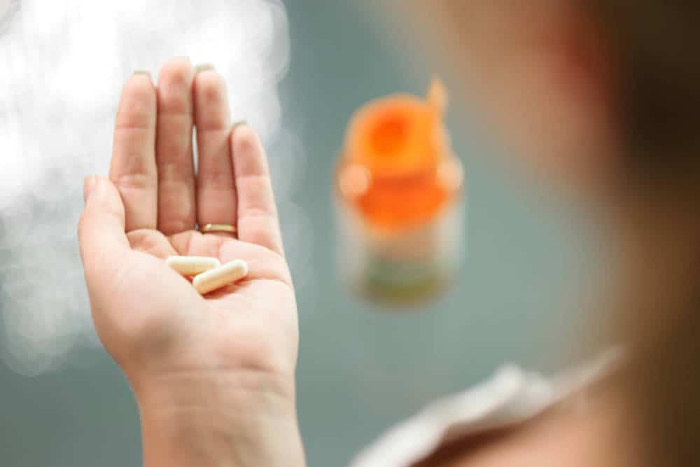 Close up view of young woman holding ginseng vitamins and minerals pills in hand with capsule bottle on table. High angle view