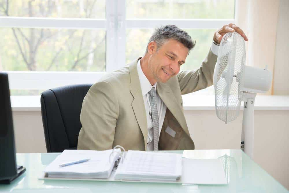 A man in an office during a hot day and using a fan to cool down.