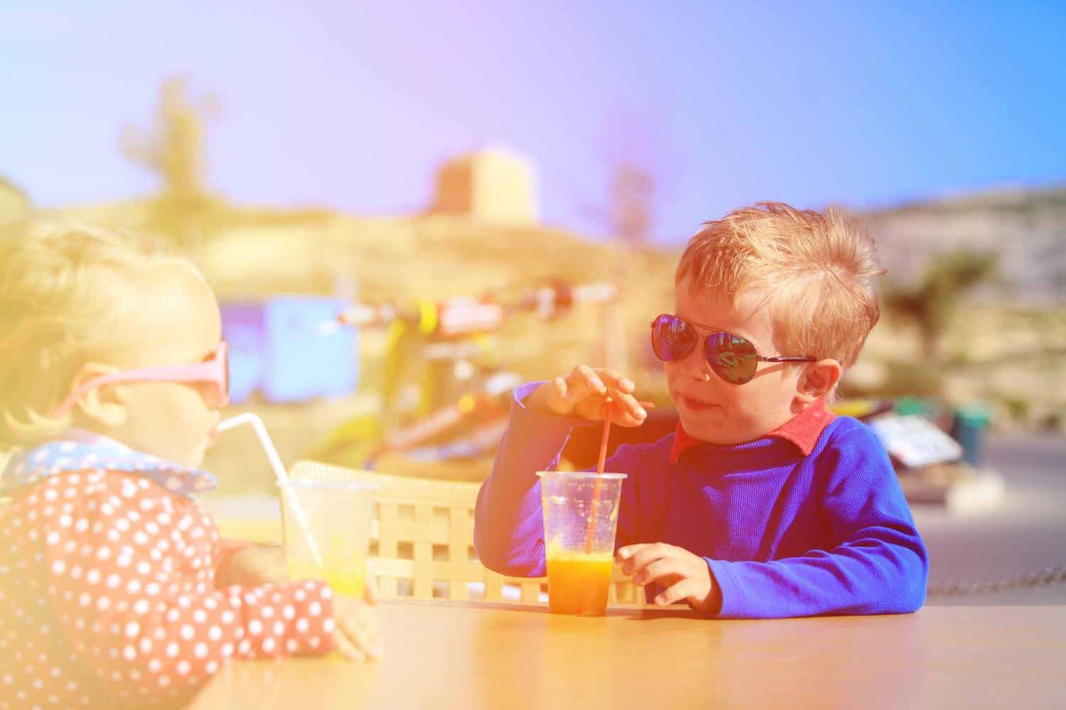 Two young children enjoying drinks at the beach.