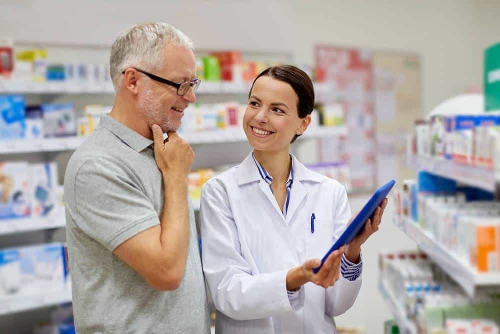 A person helping a buyer decide on medicine at a pharmacy.