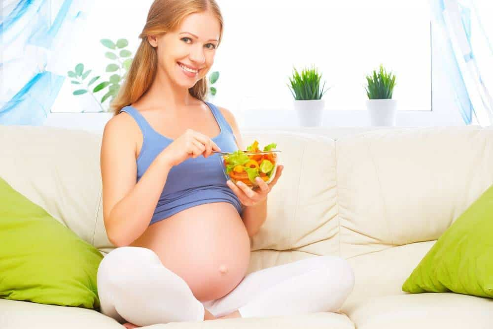 A pregnant woman eating a fruit salad.