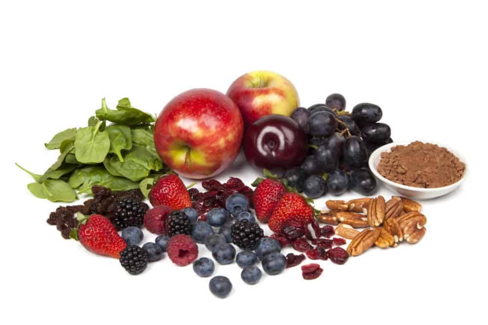 Foods rich in antioxidants, isolated on white. Includes spinach, raisins, apples, plums, red grapes, cocoa powder, pecans, cranberries, strawberries, blueberries