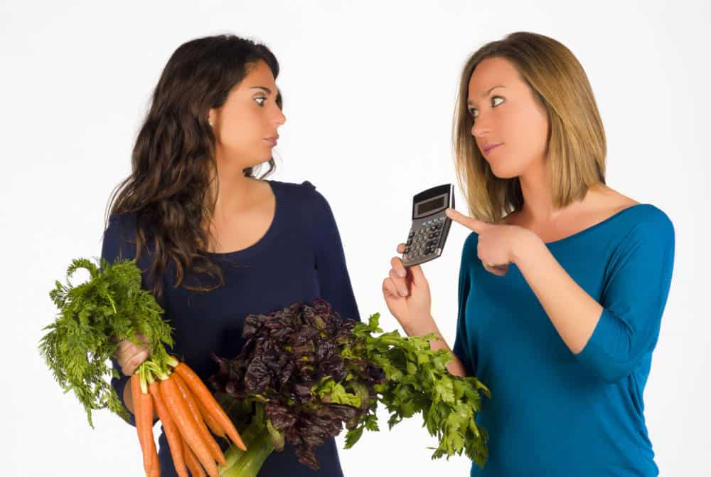 A woman showing a calculator to another woman holding vegetables.