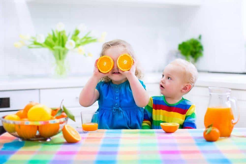 Two kids having fun with oranges.