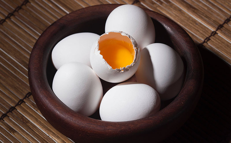 Six white eggs in a dark wooden bowl. The egg in the middle is crack open and the yolk is visible.