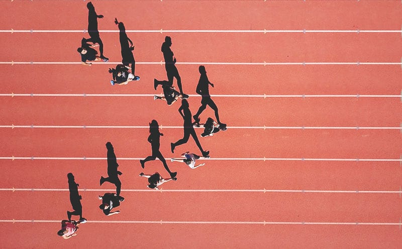 A drone shot of athletes casting long shadows on the red running track, the best one leading, after some smelling salts.