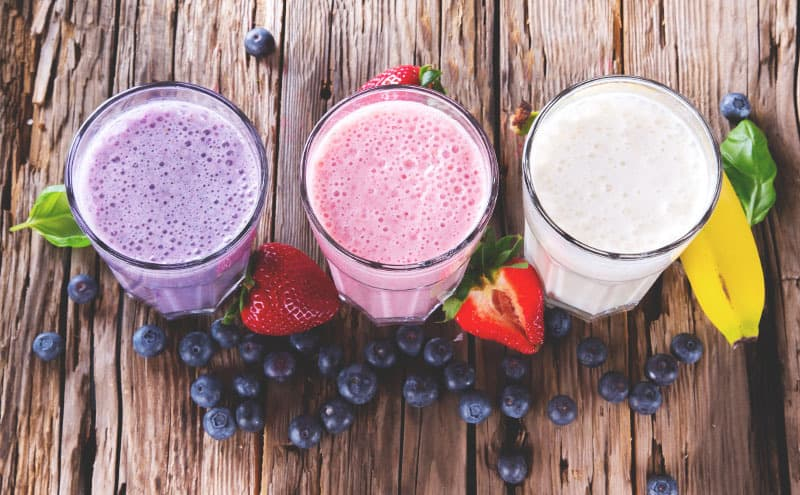 The best meal replacement shakes for diabetics in glasses, surrounded by berries, on a wooden table.