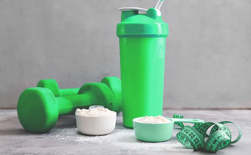 Two scoops of the best pea protein powder in front of green dumbbells and shaker on a grey stone counter.