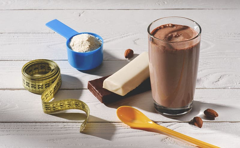 One of the best meal replacement shakes for weight loss in a glass, next to it protein bars, a spoon, a tape measure and a spoon of it in powder form.