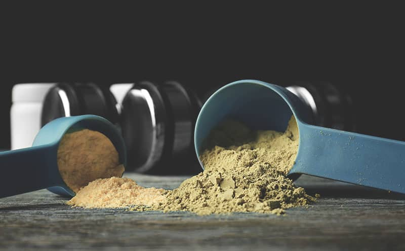 Two scoops of hemp protein powder, in front of dumbbells.