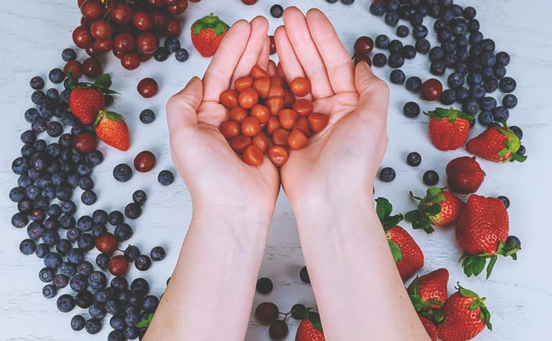 Two hands holding pieces of the best gummy multivitamin above different kinds of berries on a light background.