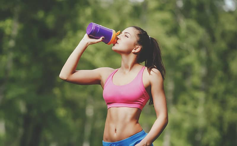 Athletic woman outdoors drinking the best pre-workout supplement for women.