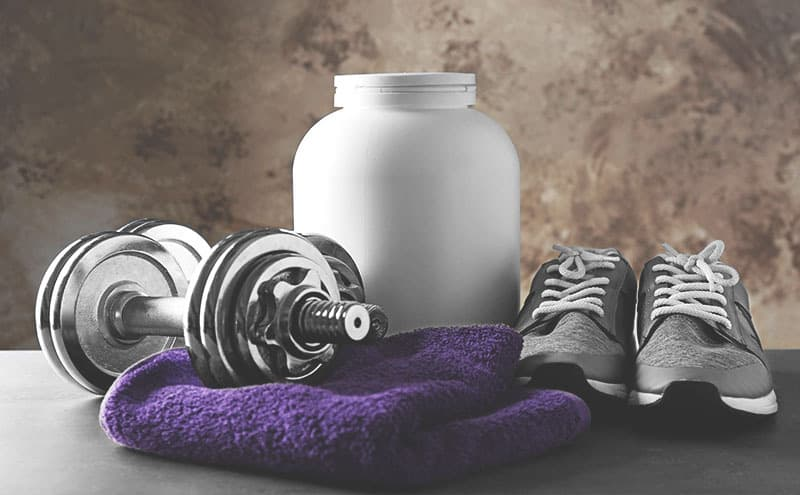 A purple towel, a dumbbell, a pair of grey shoes and the best pre-workout supplement for beginners in a big white bottle, on grey counter.