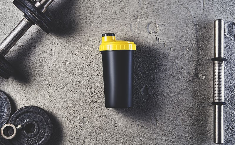 One of the best protein shakers bottles surrounded by a dumbbell, wights and a dumbbell bar, on limestone background.