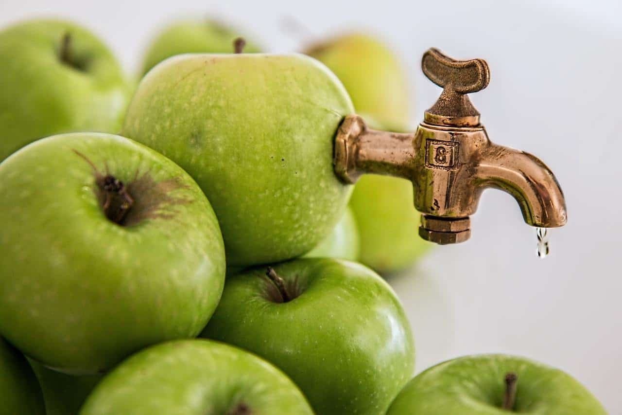 A faucet protruding from an apple.