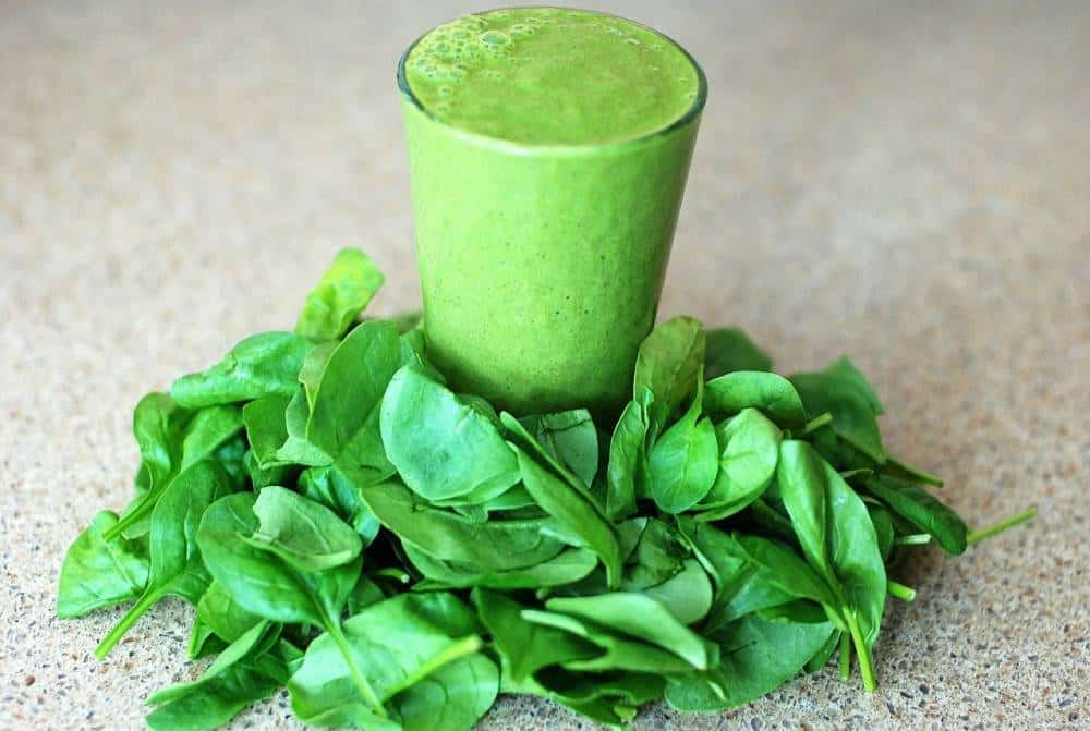 A glass of spinach juice with spinach.