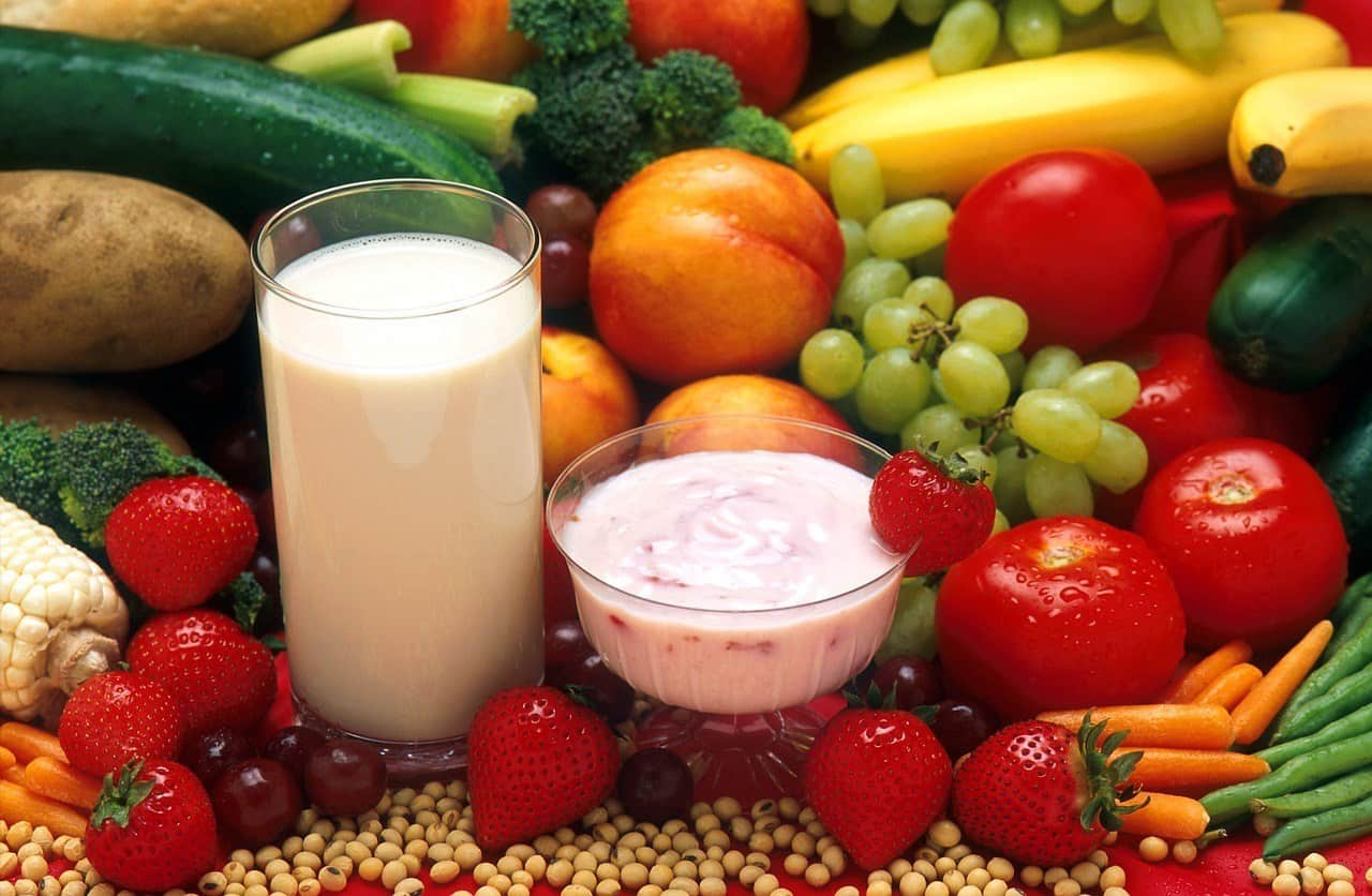 Glasses of milk and a red smoothie surrounded by fruit.
