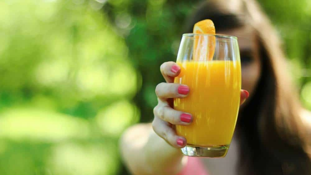A woman holding a glass of orange juice.