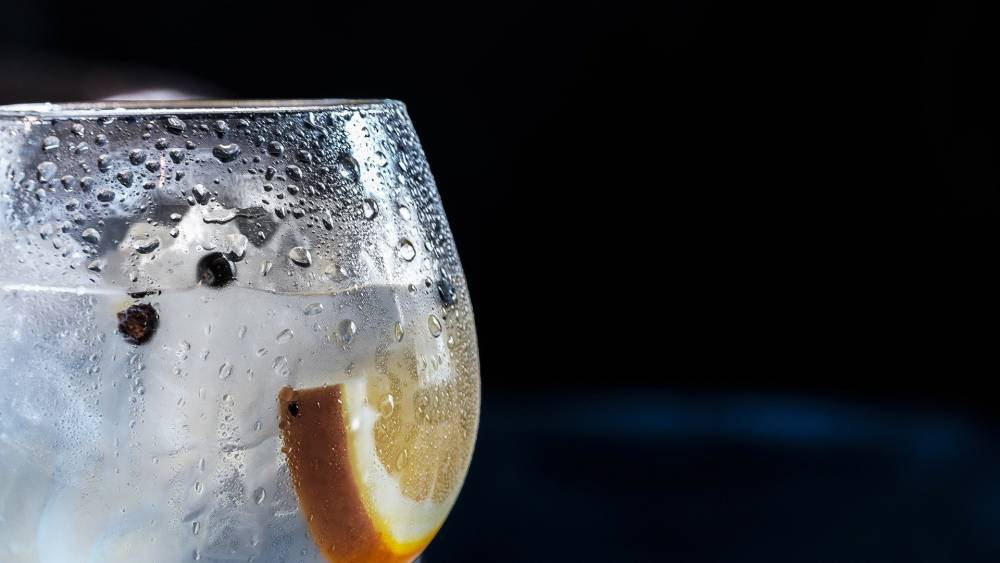 A glass of ice and water with a slice of orange.
