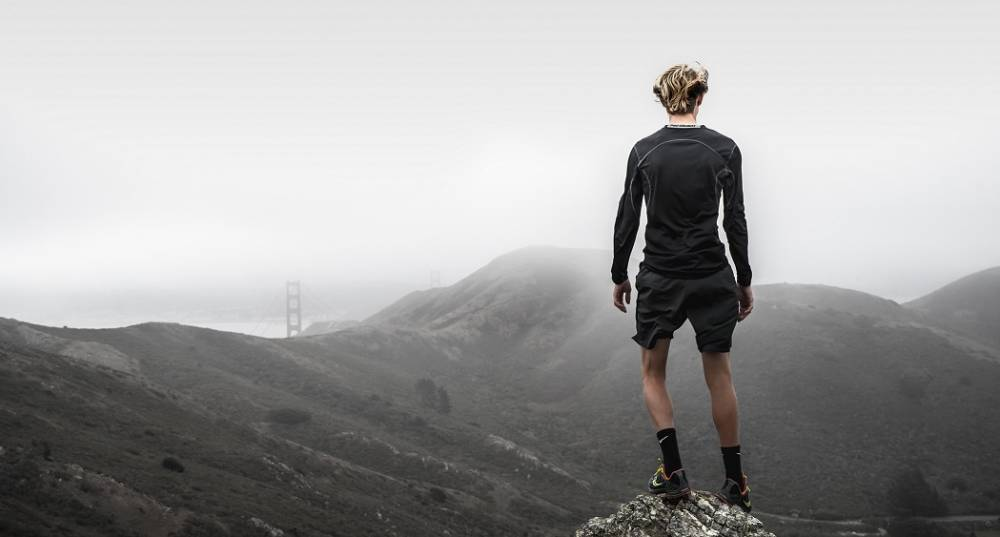 A runner standing on a hill looking at a valley.