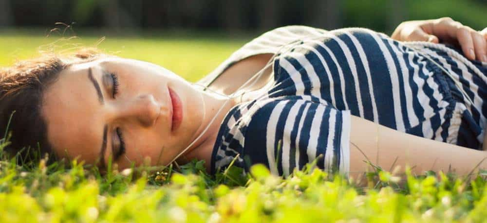 A woman sleeping in a grass.